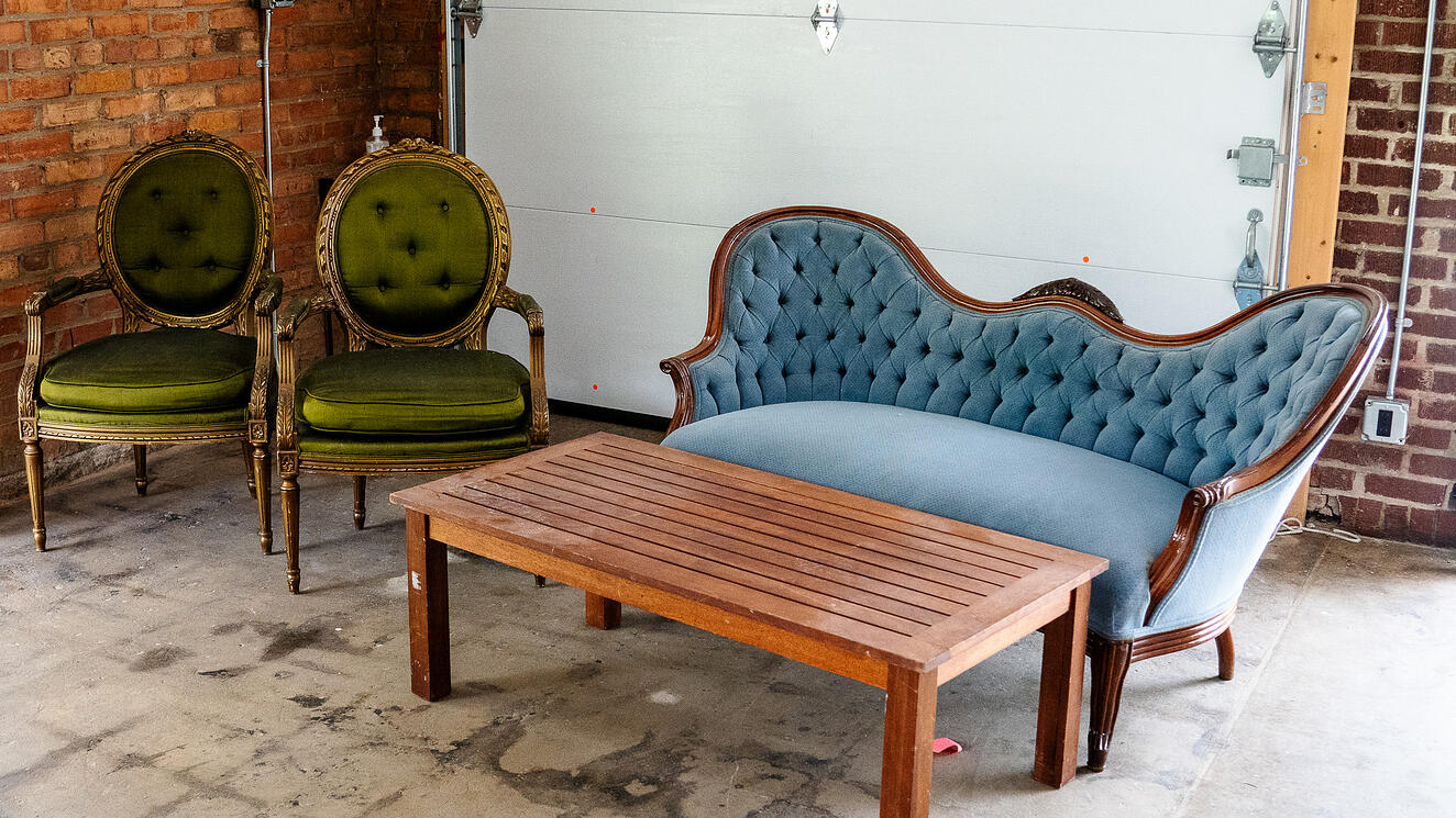 A vintage couch, coffee table and chairs.