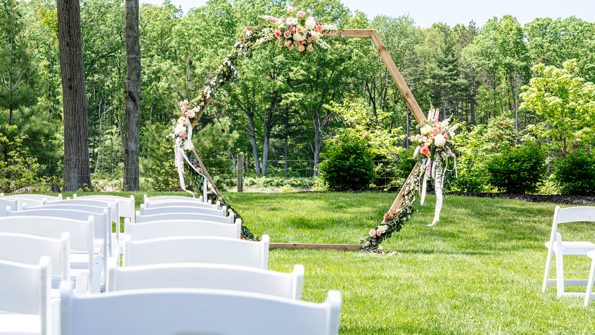A wooden arche covered in flowers and sitting at the front of a arrangement of chairs.